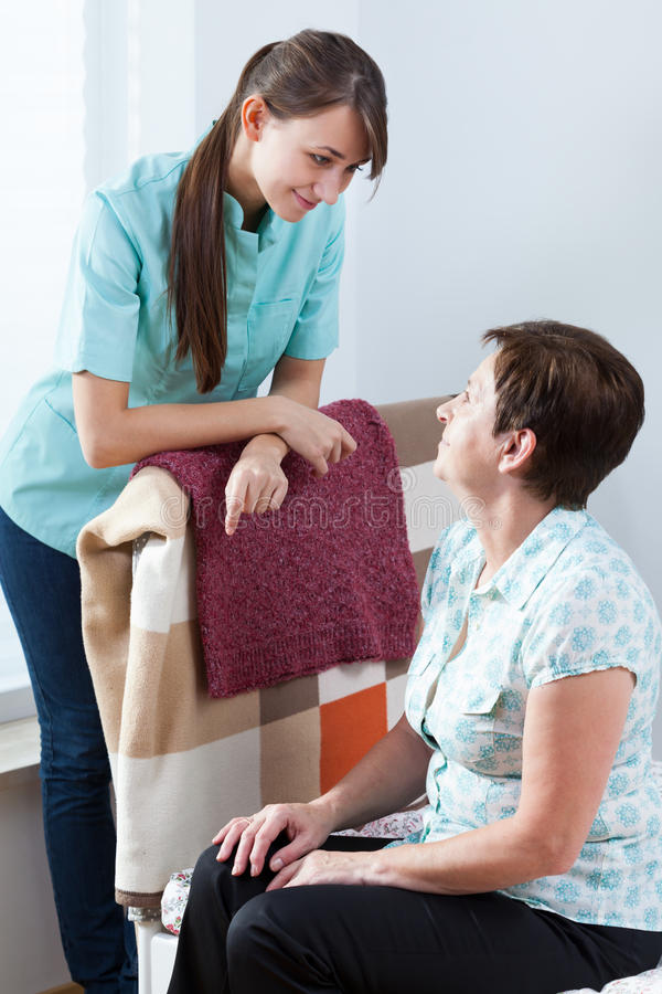 Caring nurse. Young caring nurse and her female patient royalty free stock image