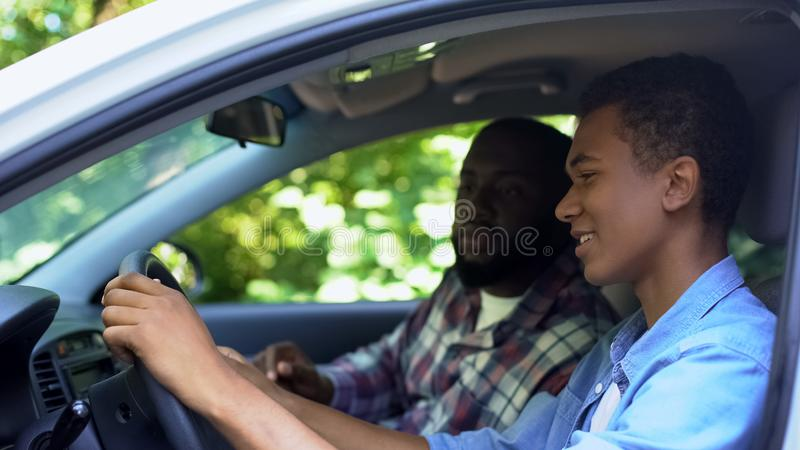 Caring parent teaching son how to drive car, spending time together, family. Stock photo stock photography