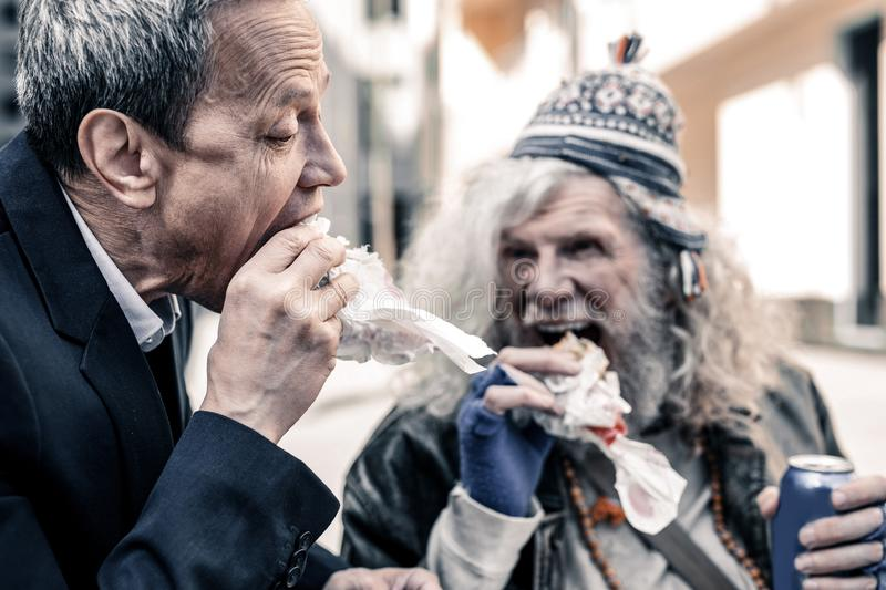 Caring short-haired business man and poor old man biting pieces of sandwich royalty free stock images