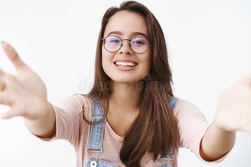 Caring tender and attractive feminine woman in glasses extending arms towards camera to give kiss and hug wanting hold royalty free stock photo
