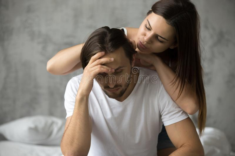 Young woman embracing upset offended man apologizing, asking for. Caring women embracing upset offended men trying to make peace cheer him up, loving wife royalty free stock images