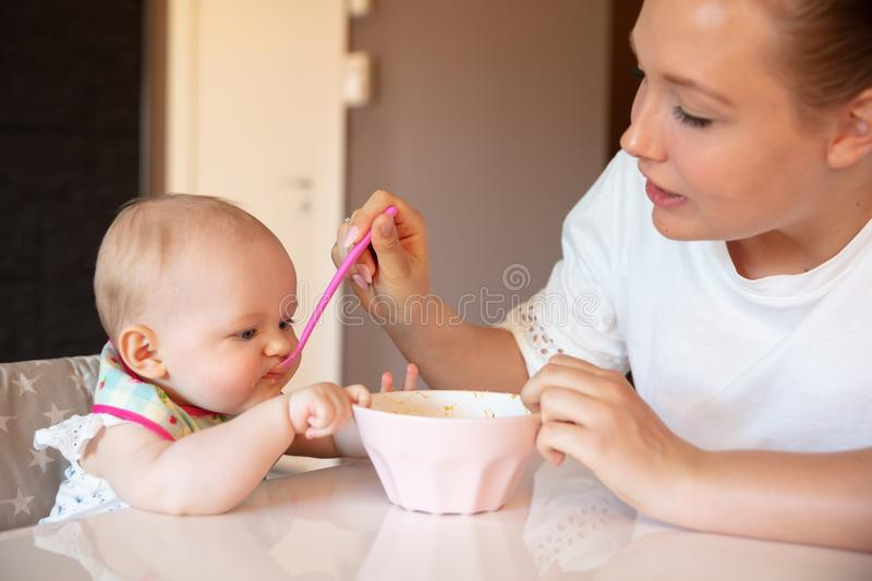 Caring young mother feeds her baby girl royalty free stock photos