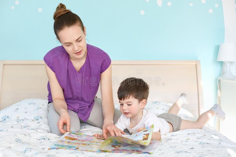 Caring young mother reads magazine with pictures for children to her small son, pose together at bed against cozy interior and stock photo