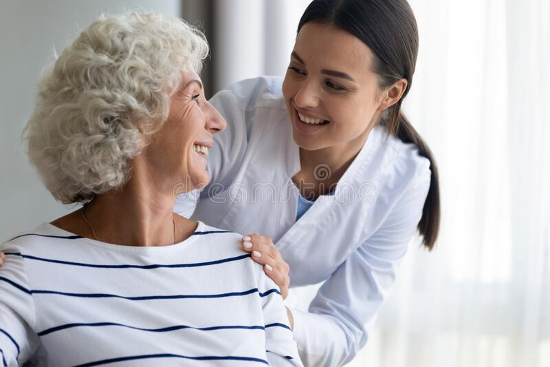 Caring young nurse assist handicapped mature female patient. Caring young nurse support assist positive old lady patient at home or hospital, smiling female stock photography