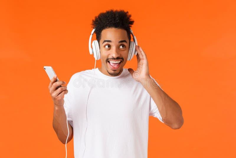 Carismático emocionado, feliz sonriente hombre afro-americano con corte de pelo afro, bigote, disfrutar de música en auriculares, fotos de archivo libres de regalías