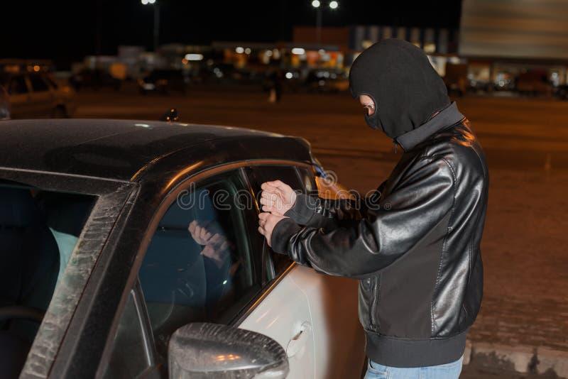 Carjacker masculino que intenta abrir la puerta de coche con la regla imagen de archivo