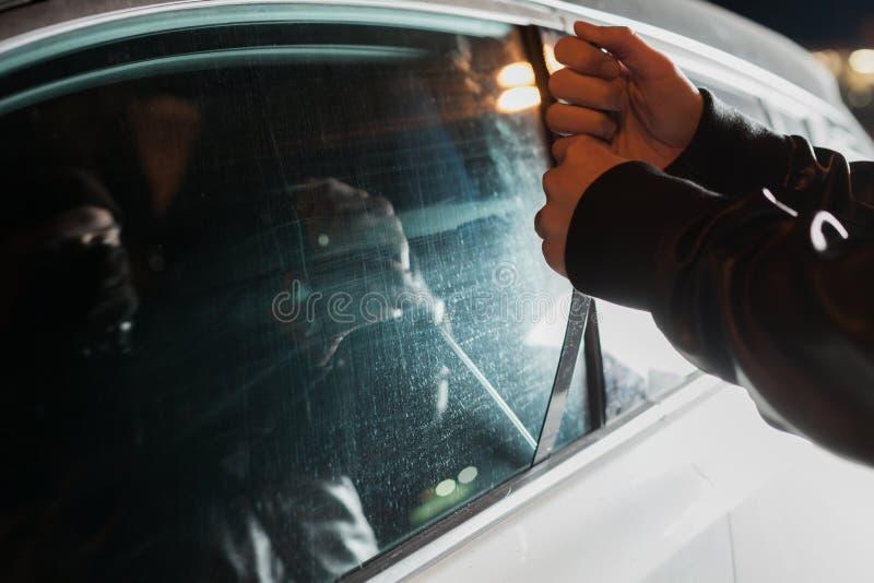 Carjacker masculino que tenta abrir a porta de carro com régua imagens de stock
