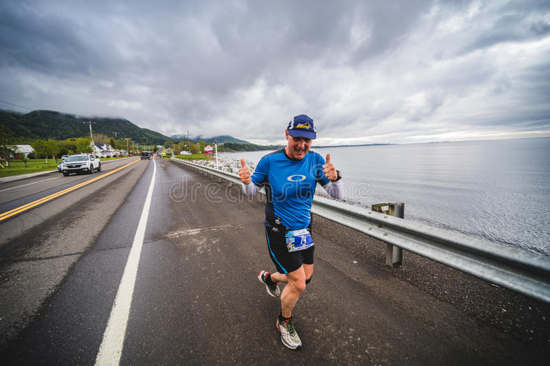 Happy Man Marathoner on the side of the Road and Ocean. CARLETON, CANADA - June 4, 2017. During the 5th Marathon of Carleton in Quebec, Canada. Happy Man royalty free stock images