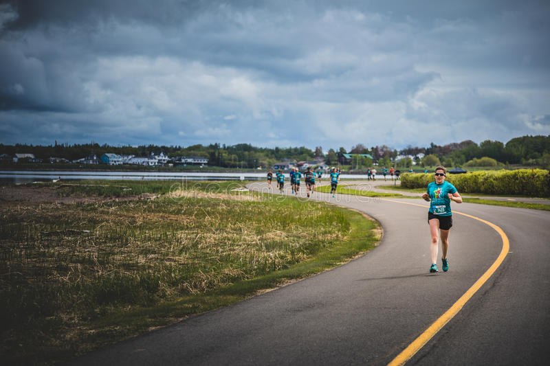 Lonely Woman Leading a Group of 10K Runners. CARLETON, CANADA - June 4, 2017. During the 5th Marathon of Carleton in Quebec, Canada. Lonely Woman Leading a Group royalty free stock photos