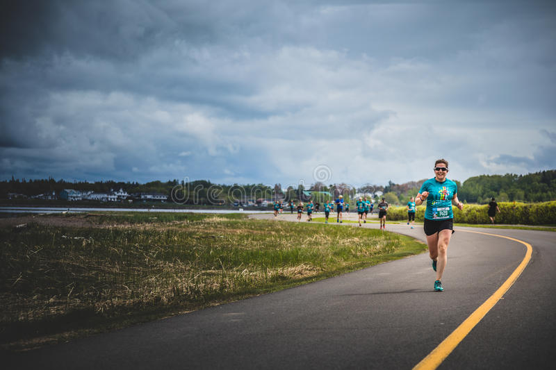 Lonely Woman Leading a Group of 10K Runners. CARLETON, CANADA - June 4, 2017. During the 5th Marathon of Carleton in Quebec, Canada. Lonely Woman Leading a Group royalty free stock images