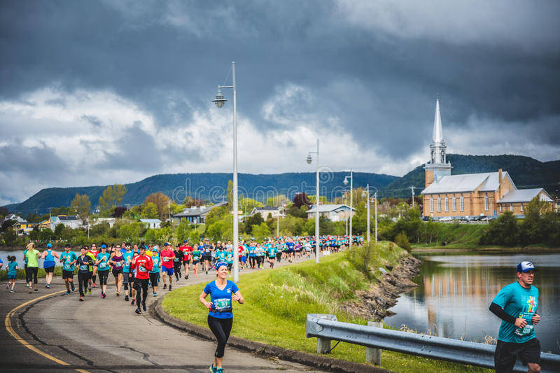 Marathoners in both sides of the street in a little city with ch. CARLETON, CANADA - June 4, 2017. During the 5th Marathon of Carleton in Quebec, Canada royalty free stock image