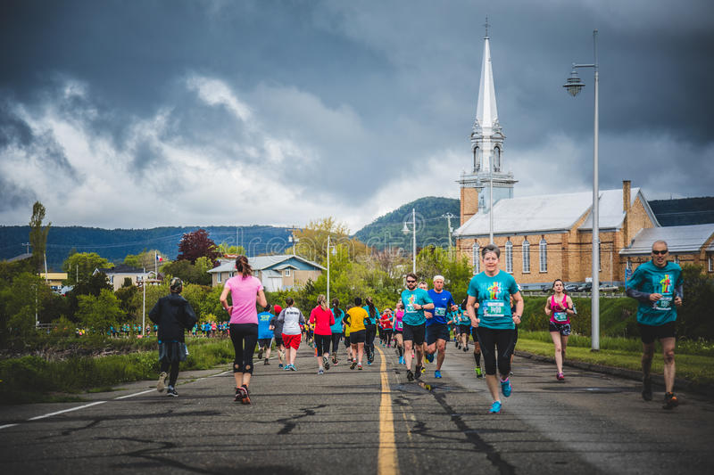 Marathoners in both sides of the street in a little city with ch. CARLETON, CANADA - June 4, 2017. During the 5th Marathon of Carleton in Quebec, Canada stock image