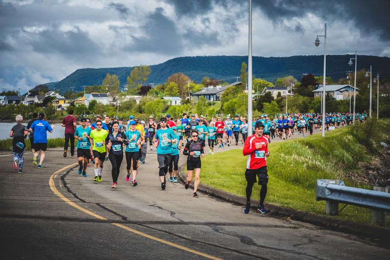 Marathoners in both sides of the street in a little city. CARLETON, CANADA - June 4, 2017. During the 5th Marathon of Carleton in Quebec, Canada. Marathoners in royalty free stock photo