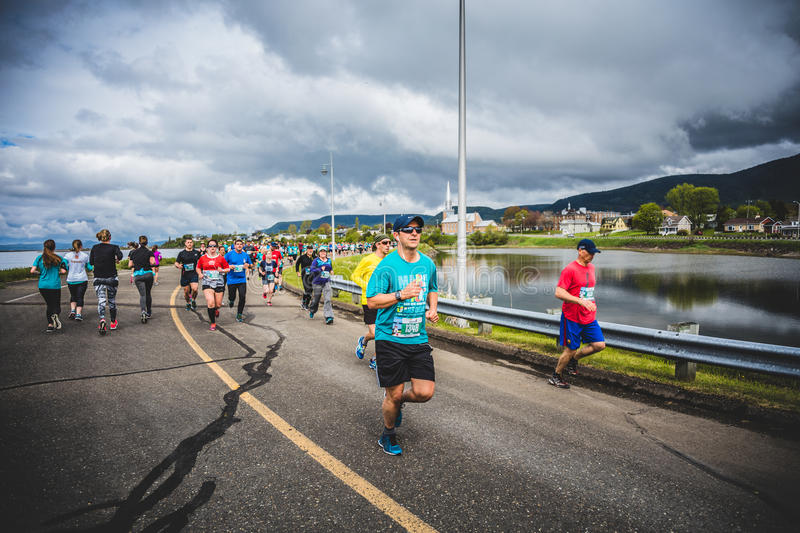 Marathoners in both sides of the street in a little city with ch. CARLETON, CANADA - June 4, 2017. During the 5th Marathon of Carleton in Quebec, Canada stock images