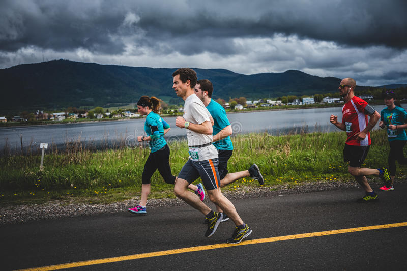 Group of 10K Runners in front of a beautiful Mountain Landscape. CARLETON, CANADA - June 4, 2017. During the 5th Marathon of Carleton in Quebec, Canada. Group of royalty free stock images