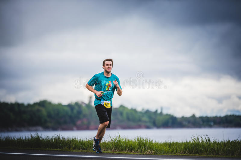 Young Man Marathoner at about 7km of distance Alone on the side. CARLETON, CANADA - June 4, 2017. During the 5th Marathon of Carleton in Quebec, Canada. Young royalty free stock photos