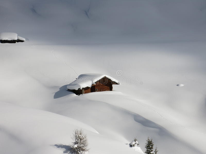 Carlingue de rondin dans la neige profonde dans les Alpes du sud du Tyrol  photographie stock libre de droits
