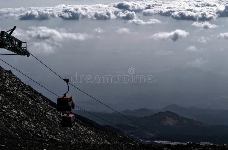 Carlingues d'un funiculaire s'élevant au-dessus des nuages sur le mont Etna photographie stock libre de droits