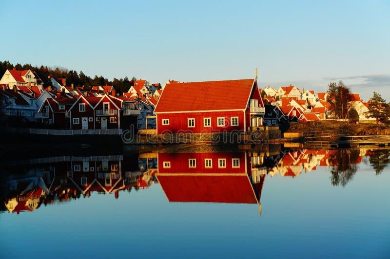 Carlingues en bois rouges au terrain de camping par le fjord photographie stock libre de droits