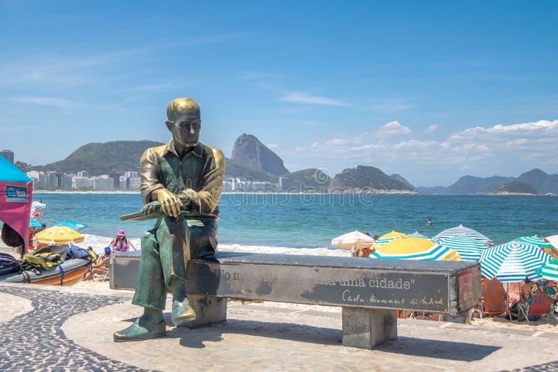 Carlos Drummond de Andrade Statue en la playa de Copacabana con Sugar Loaf Mountain en fondo - Rio de Janeiro, el Brasil imágenes de archivo libres de regalías