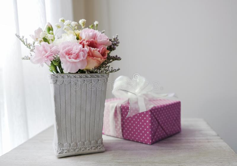 Carnation flower in cement pot and pink gift box. On vintage cabinet at the bedroom royalty free stock image