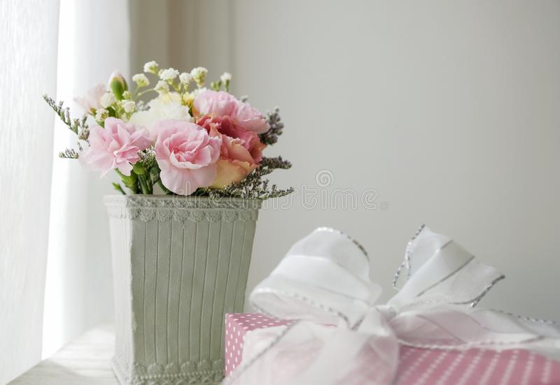Carnation flower in cement pot and pink gift box. On vintage cabinet at the bedroom stock photos