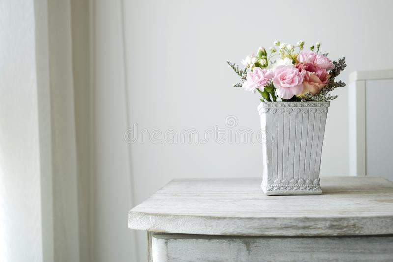 Carnation flower in cement pot on vintage cabinet at the bedroom. With copy space stock images