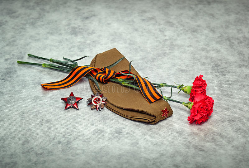 Carnation flowers, George Ribbon, forage cap, orders and medals stock photography