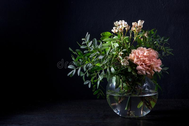 Carnations and pistachio sprigs in a glass vase with water royalty free stock photo