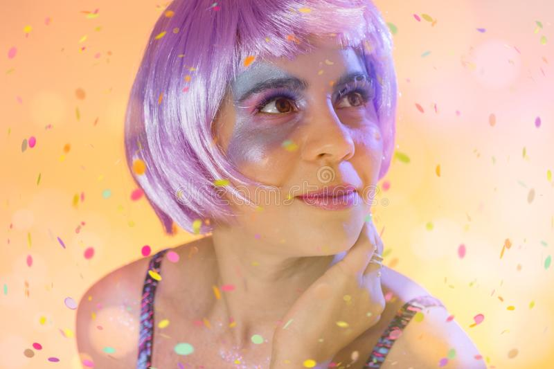Carnaval Brazil Confetti. Face of brazilian girl wearing purple wig and makeup mask. Color background. Masquerade concept,. Carnaval Brazil Confetti. Happiness stock images