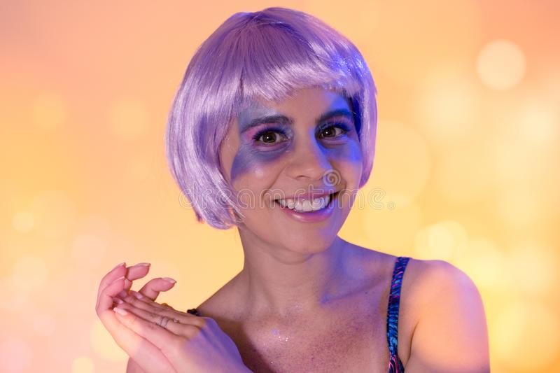 Carnaval Brazil. EFace of brazilian girl wearing purple wig and makeup mask. Colorful background. Carnival concept, fun and party. Carnaval Brazil. Excited and stock photo