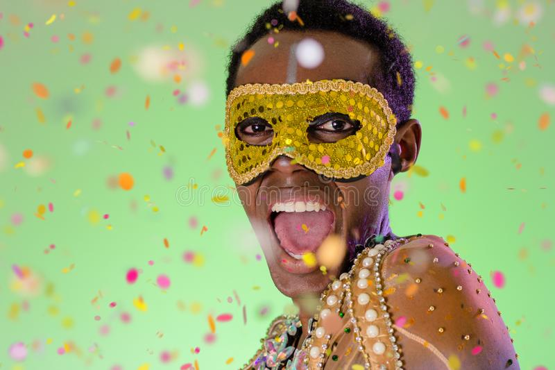 Carnaval Brazil. Excited and Cheerful. Throwing confetti. Portrait of black man dressed up for the holiday. Bright background. royalty free stock images
