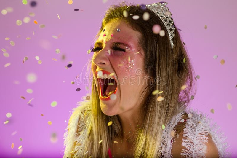 Carnaval Brazil. Excited and Cheerful. Throwing confetti. Portrait of brazilian girl with fun costume. Colorful background. Carnival concept, fun and party stock photos