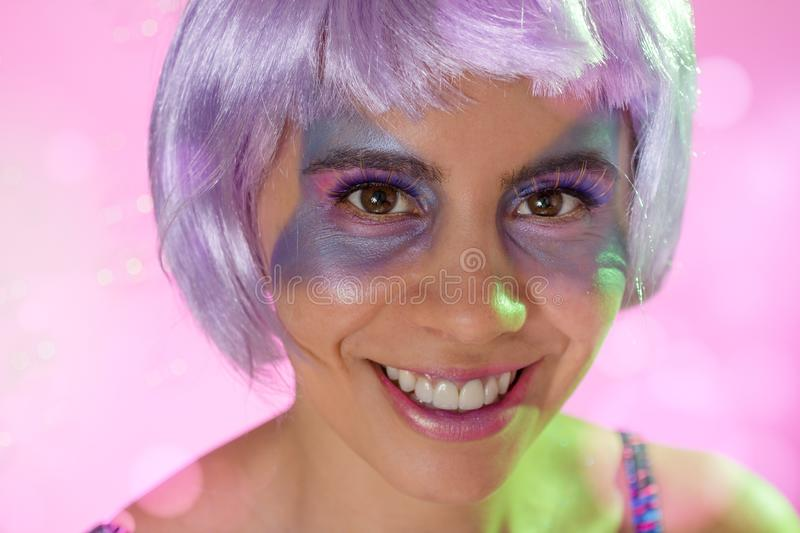 Carnaval Brazil. Face of brazilian girl wearing purple wig and makeup mask. Bright and Colorful. Holiday concept, tradition and royalty free stock image