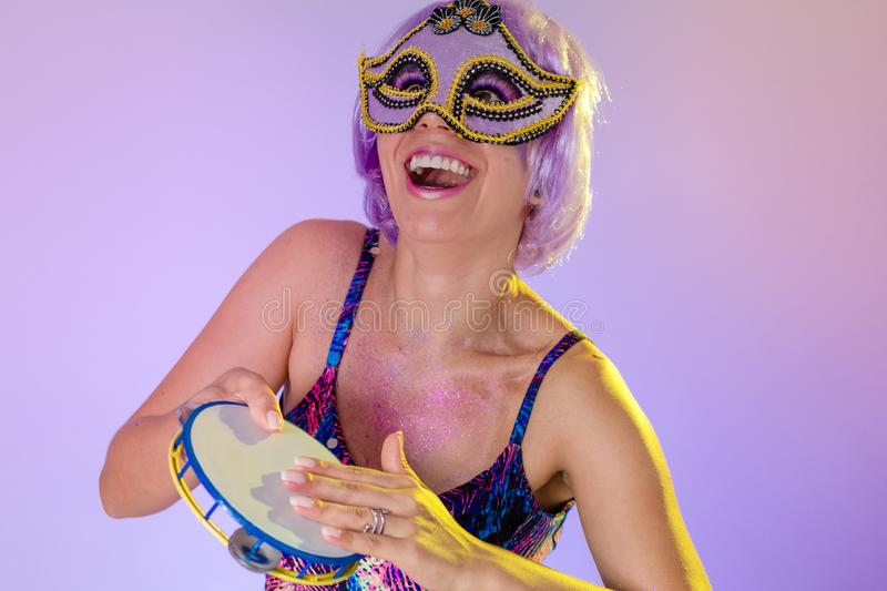 Carnaval Brazil Tambourine. Portrait of latin girl with violet wig and make up mask. Bright and Colorful. Holiday concept,. Carnaval Brazil Tambourine. Excited stock images