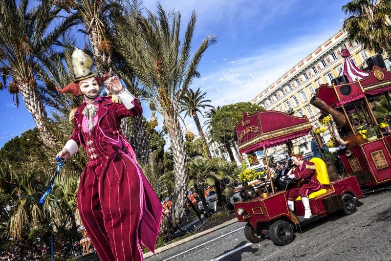 Carnaval de Nice, bataille de ` de fleurs Un échassier dans le costume rouge et un peu de train photographie stock