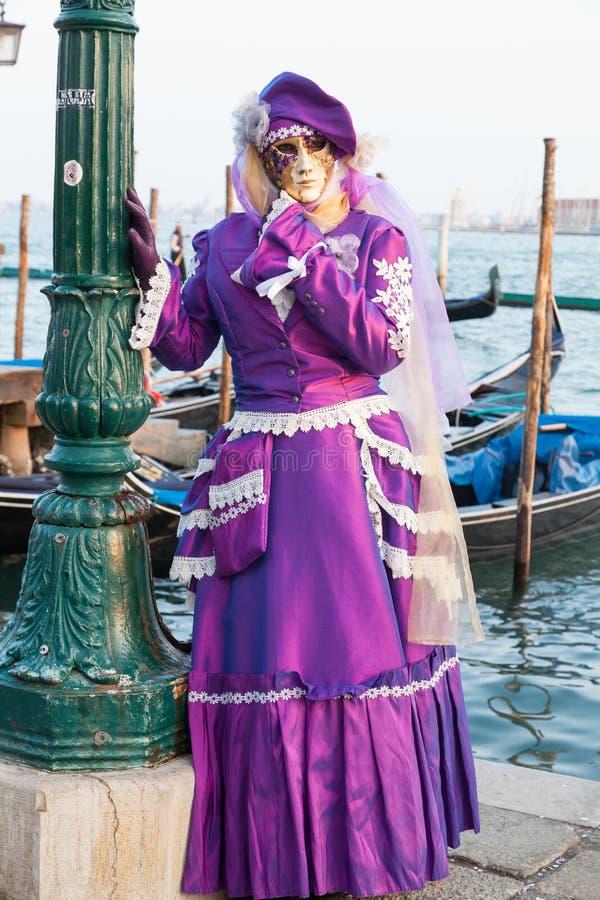 Carnaval de Venise, Italie Femme dans la robe pourpre avec des gondoles photos stock