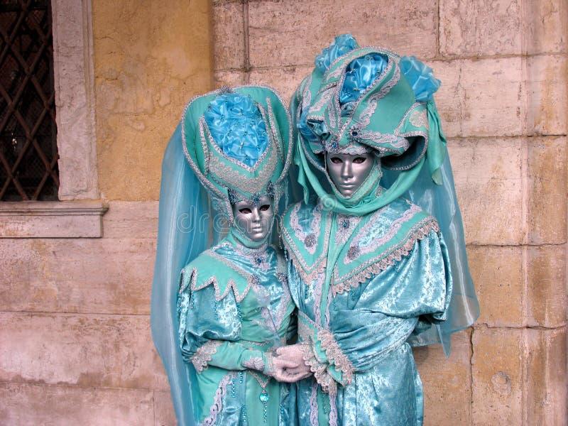 Carnaval : deux masques dans des costumes de turquoise, retenant des mains images stock