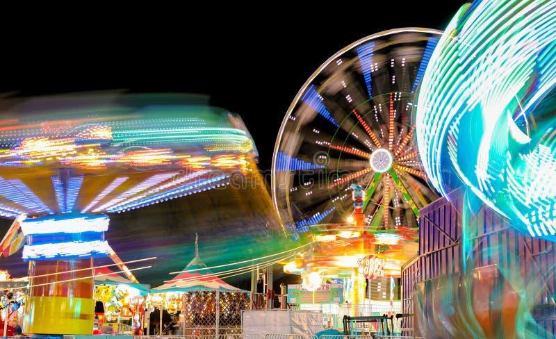 Carnaval e Ferris Wheel em luzes de giro da noite foto de stock royalty free