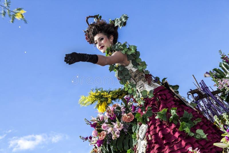 Carnaval famoso de Niza, batalla del ` de las flores Un actor de la mujer lanza mimosas imagenes de archivo