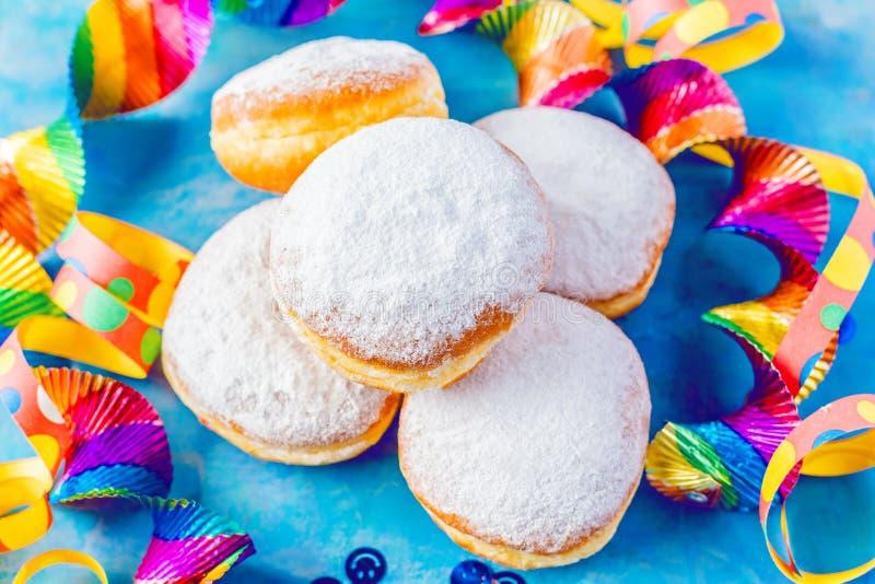 Carnaval gepoederde suiker donuts met document wimpels stock afbeeldingen
