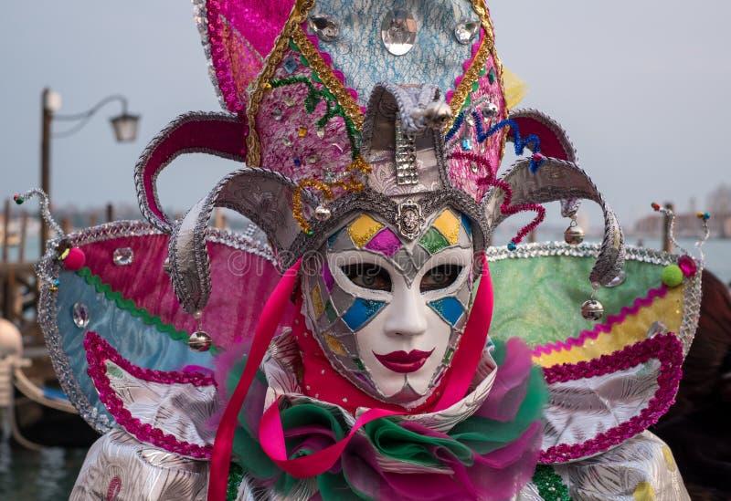 Carnaval -Carnaval-goer in traditioneel kostuum die zich met terug naar Grand Canal, met gondels op achtergrond, tijdens Venetië  royalty-vrije stock foto