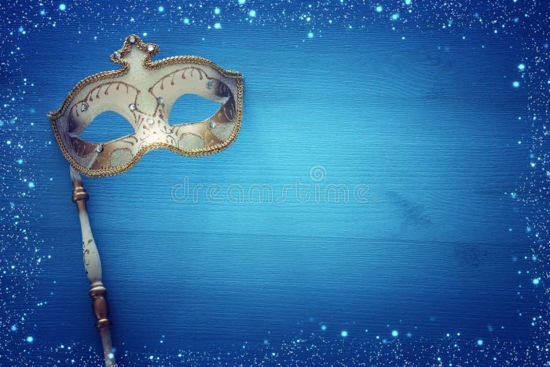 Carnaval-het concept van de partijviering met elegant gouden masker op stok over blauwe houten achtergrond Hoogste mening royalty-vrije illustratie
