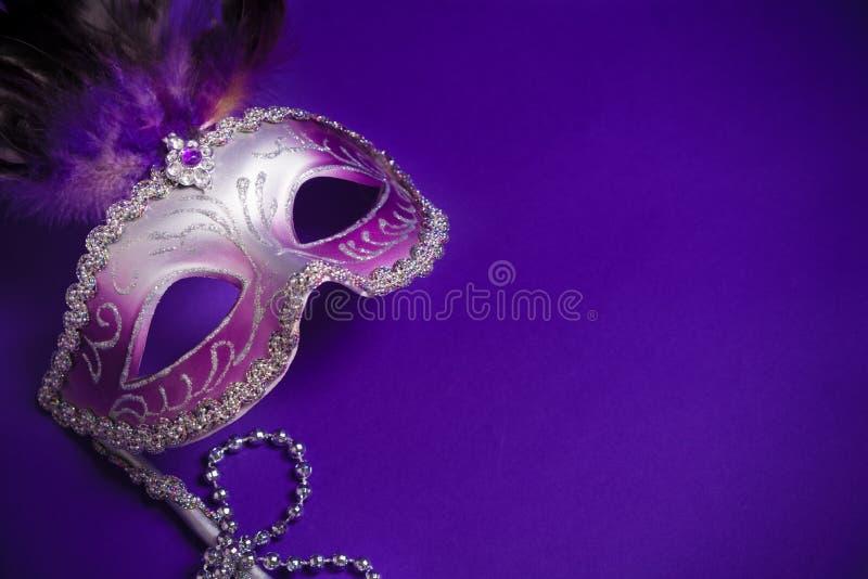 Carnaval púrpura o máscara veneciana en fondo púrpura fotos de archivo