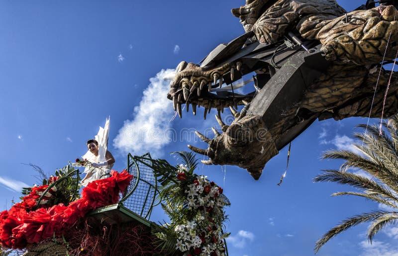Carnaval van Nice, Bloemen` slag De jonge vrouw kleedde zich in wit en een draak royalty-vrije stock afbeelding