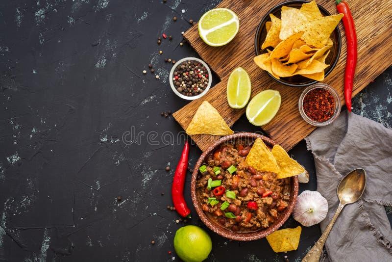 Carne жулика Chili с nachos откалывает на деревенской предпосылке Мексиканская еда Место для текста, взгляд сверху стоковое изображение