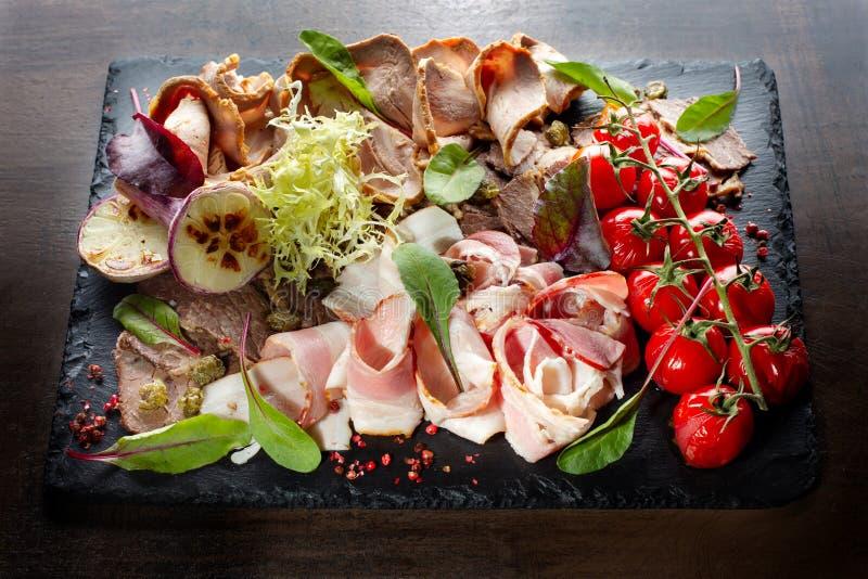 Carne affettata, prosciutto, pomodoro, capperi, aglio sul fondo nero dell'ardesia fotografia stock libera da diritti