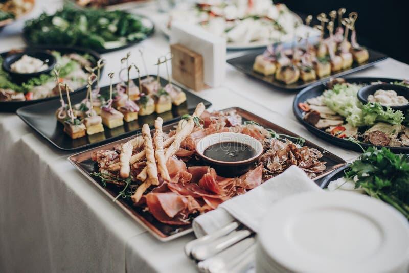 Carne affumicata, salsa, prosciutto di Parma, aperitivi dell'insalata sulla tavola a nozze o concetto d'approvvigionamento di lus fotografie stock