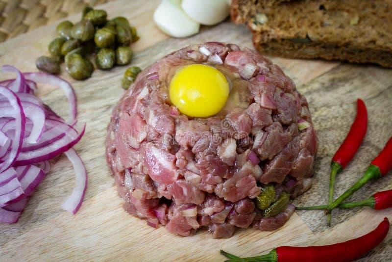 Carne alla tartara saporita, manzo crudo - carne alla tartara classica sul bordo di legno immagine stock