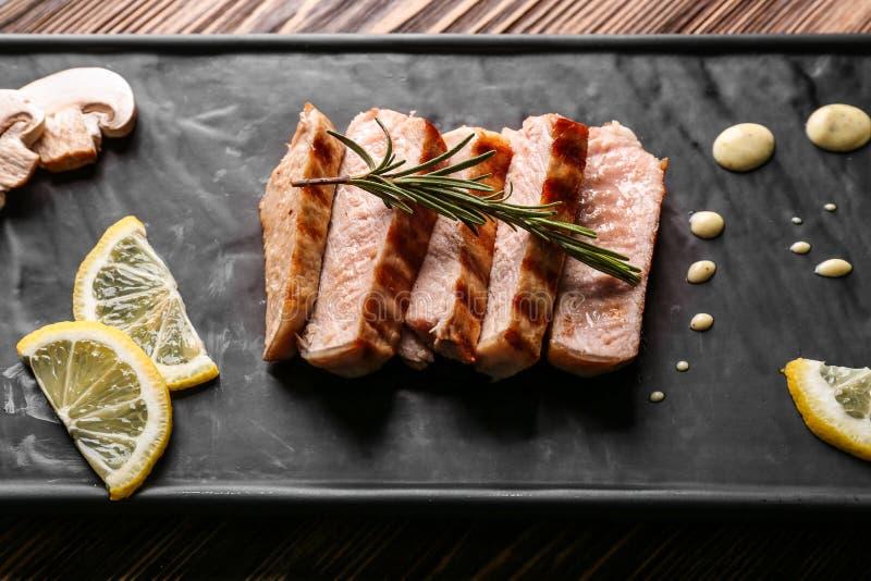 Carne arrostita deliziosa con il limone e la salsa sul vassoio fotografie stock libere da diritti